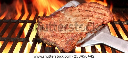 BBQ Roasted Beef Steak on the Turner and Flaming Charcoal Grill