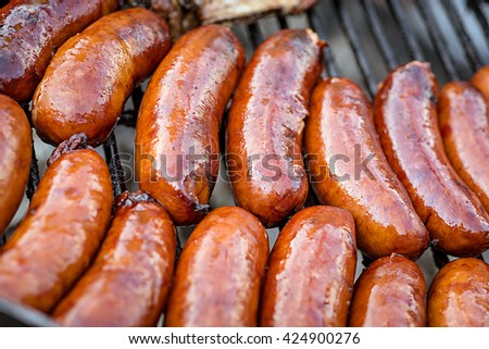 BBQ with fiery group of sausages on the grill - stock photo