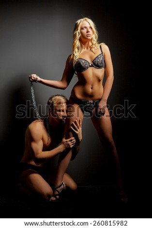 BDSM concept. Imperious mistress and submissive - stock photo