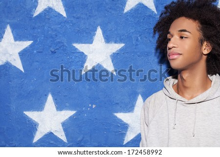 Be cool! Young African man standing against American flag and looking away - stock photo