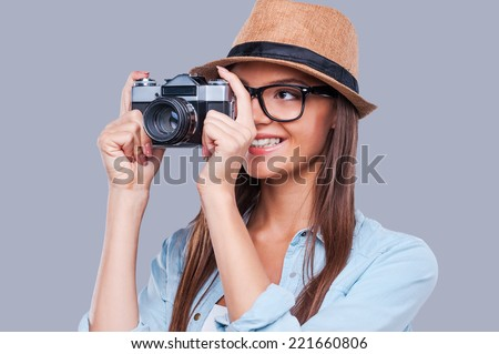 Be creative! Creative young girl taking a photograph and smiling while standing against grey background - stock photo