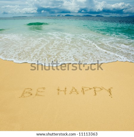 be happy written in a sandy tropical beach - stock photo