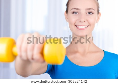 Be healthy. Selective focus of pleasant young lady holding her hands in front of her and keeping dumbbell while doing exercises. - stock photo