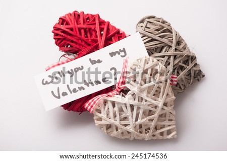 Be my Valentine. Closeup image of lovely decorative colored hearts with a card and ribbon beautifully arranged on white background - stock photo
