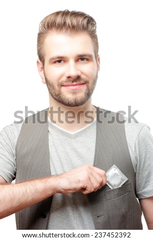 Be safety! Young handsome smiling man with beard putting a condom into his waistcoat pocket. Isolated on white background. - stock photo