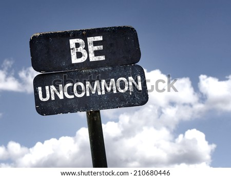 Be Uncommon sign with clouds and sky background  - stock photo