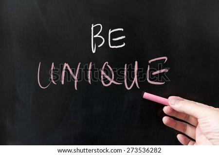 Be unique words written on blackboard using chalk - stock photo