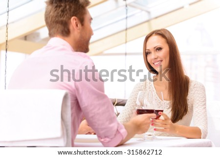 Be with me forever. Beautiful blissful couple sitting at the table and drinking wine while dining in the restaurant