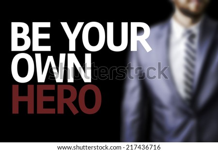 Be your Own Hero written on a board with a business man on background - stock photo