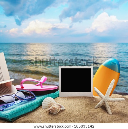 beach accessories and photos on the memory on a background of sea and sand - stock photo