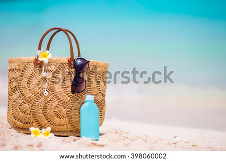 Beach accessories - straw bag, headphones, bottle of cream and sunglasses on the beach - stock photo