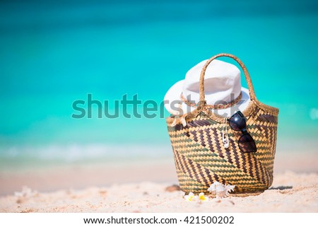 Beach accessories - straw bag, sunglasses, hat on the beach - stock photo