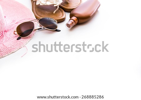 Beach accessories. Summer shoes and hat with sunglasses and suntan lotion on a white background - stock photo