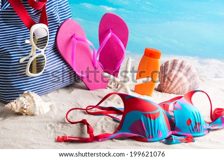 Beach accessories with colorful swimming suit  - stock photo
