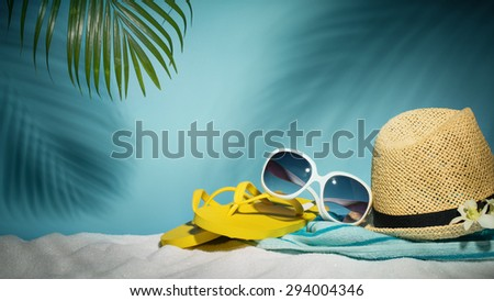 Beach accessories with sunglasses,hat,flip-flop and towel on sands - stock photo
