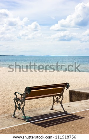 Beach and bench in sunny day with cloud - stock photo