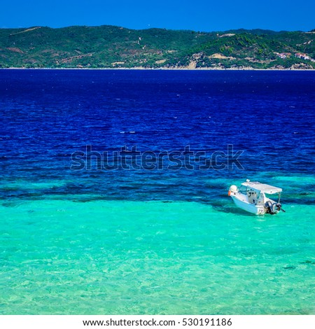Beach at sunny day with clear blue sky, turquoise sea water and bouts. Photo from Megali Amos or the Big sandy beach, Ammouliani Island, Athos, Halkidiki, Northern Greece.