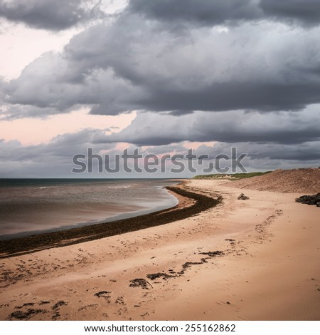 Beach at sunset in Prince Edward Island, Canada with dark cloudy sky, square format - stock photo