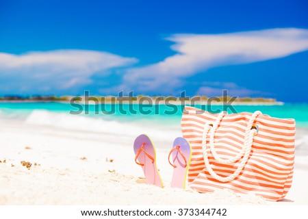 beach bag and flip flops on berfect caribbean white sand - stock photo