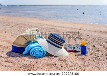 Beach Bag and Supplies for Day at the Beach on Shore with Deserted Beach in Background - Sun Hat, Flip Flops, Towel, Sunscreen Lotion, and Beach Bag on Sunny Beach - stock photo