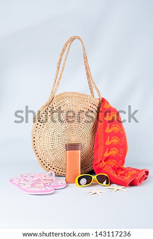 beach bag,towel,sunglasses,flip flops,cream and starfishes on blue background - stock photo