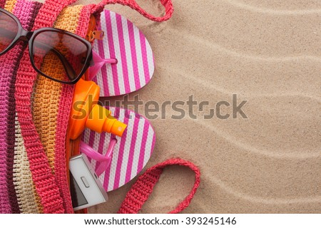 Beach bag with sunscreen, flip flops, cellphone, sunglasses. Summer holiday background