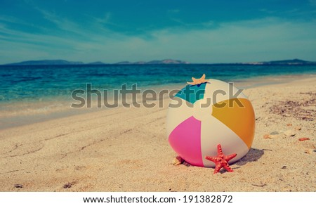 beach ball by a turquoise shore in vintage tone - stock photo