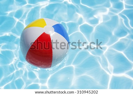 Beach ball floating in swimming pool abstract concept for summer vacations, relaxation and fun in the sunshine - stock photo