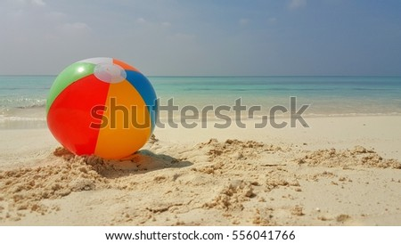 Beach ball on a white sandy with blue sea and sky at sunrise sunset