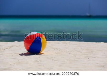 beach ball on tropical sand beach - stock photo