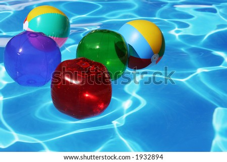 Beach balls floating in blue pool