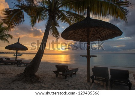 Beach beds and umbrella on the beach , Mauritius - stock photo