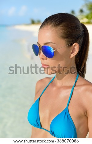 Beach bikini Asian woman wearing fashion eye wear. Young female adult model with trendy blue mirrored aviator mirror sunglasses and turquoise swimwear top looking at the ocean. - stock photo