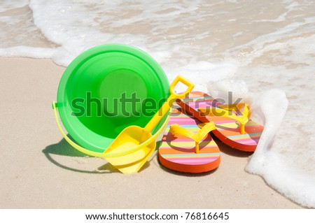 beach bucket and flip flops - stock photo