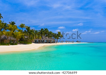 Beach bungalows on a tropical island - vacation background - stock photo