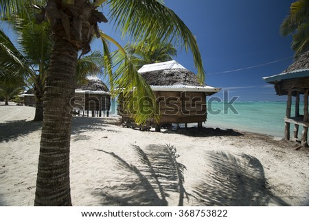 beach bungalows on  white sand beach with palm tree and view on azure sea  in polynesia - stock photo