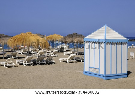 beach cabin stripped blue on white and deckchairs on the costa Adeje at Tenerife in the Spanish Canary Islands - stock photo