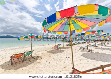 Beach chair and colorful umbrella on the beach in sunny day, Phuket Thailand - stock photo