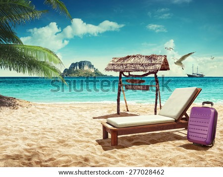 Beach chair and suitcase on sand beach. Concept for rest - stock photo