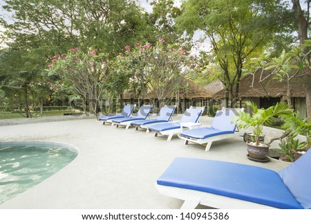 Beach chair and Swimming pool - stock photo