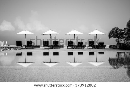 Beach chair and white umbrella on swimming with ocean view on black and white color - stock photo