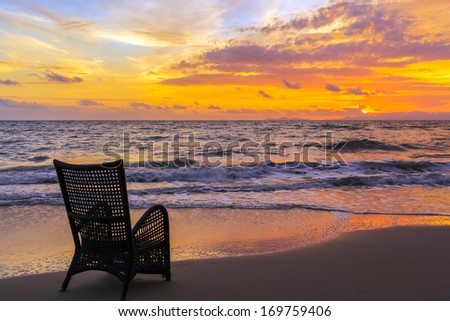 Beach chair on sand beach for relaxing in sunset