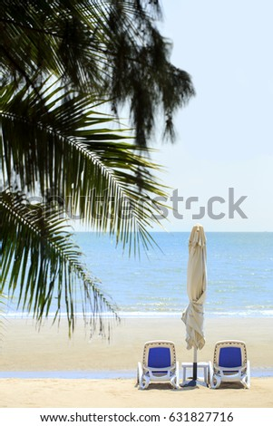 Beach chair on the beach with coconut tree