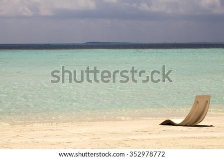 Beach chair on the white sand beach with cloudy blue sky and sun - stock photo
