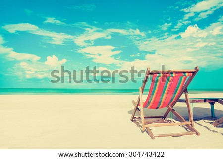 Beach chair on white sand beach in sunny sky background, vintage tone - summer holiday concept - stock photo