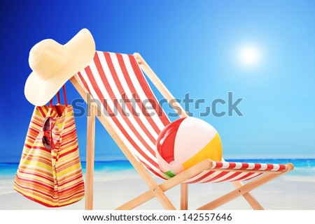 Beach chair with ball, bag and hat at sunny day by the sea - stock photo
