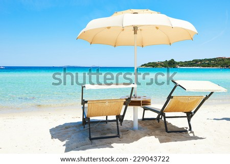 Beach chair with umbrella for rest and relaxation on resort sand beach - stock photo