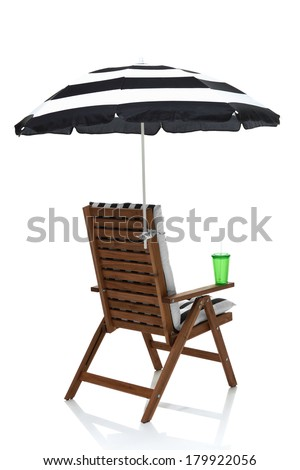Beach chair with umbrella, towel and drink behind angle view - stock photo
