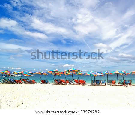 Beach chairs and colorful umbrella on the beach in sunny day, Phuket Thailand