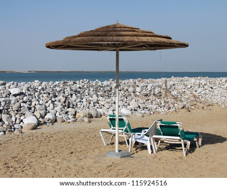 Beach chairs and grass umbrellas at sea - stock photo